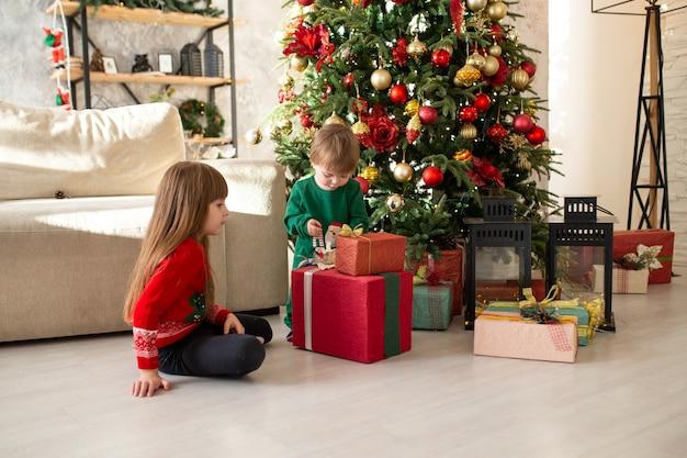 Belle petite fille jouant avec son frère et cadeau de noël