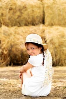 Belle petite fille joyeuse dans un chapeau de paille sur le foin