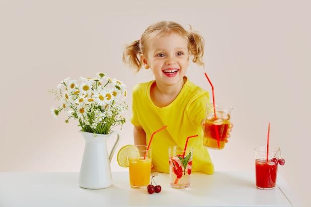 Une belle petite fille joyeuse dans un t-shirt jaune avec plusieurs boissons gazeuses et cocktails de baies.