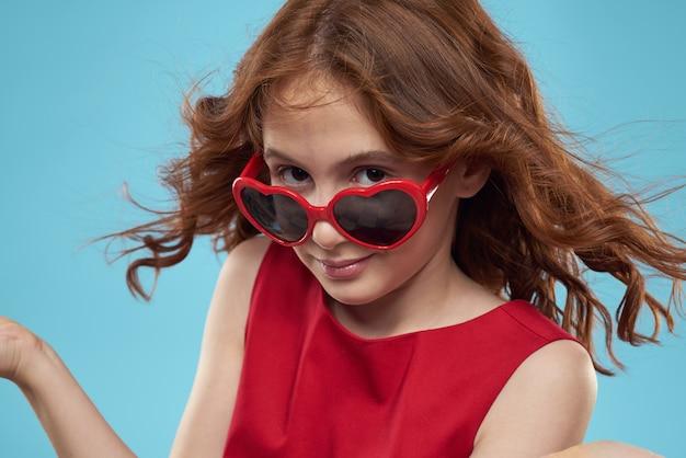 Belle petite fille à lunettes coeur et une robe rouge, princesse, joli bébé sur un mur bleu