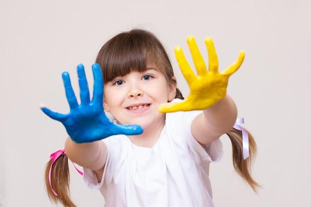Belle petite fille avec les mains dans la peinture