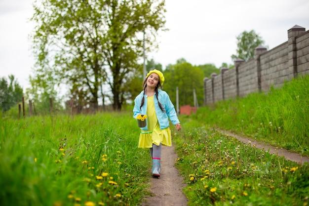 Une belle petite fille marche dans la campagne le long d'un chemin près d'une pelouse verte avec des pissenlits