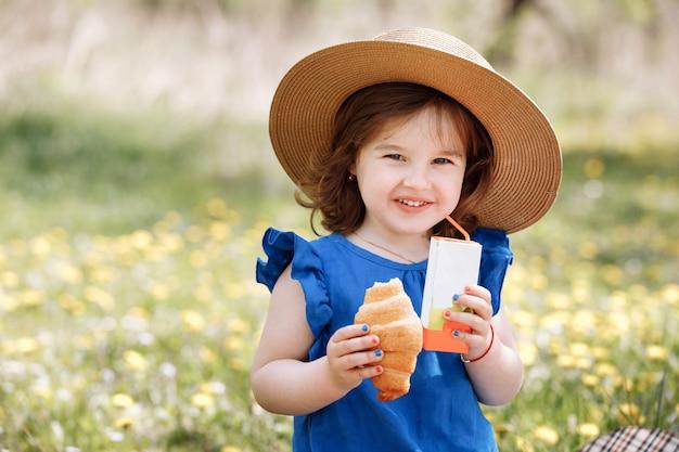 Une belle petite fille mignonne rit et s'amuse dans un chemisier bleu avec une fleur de cerisier en fleurs dans un jardin de printemps.