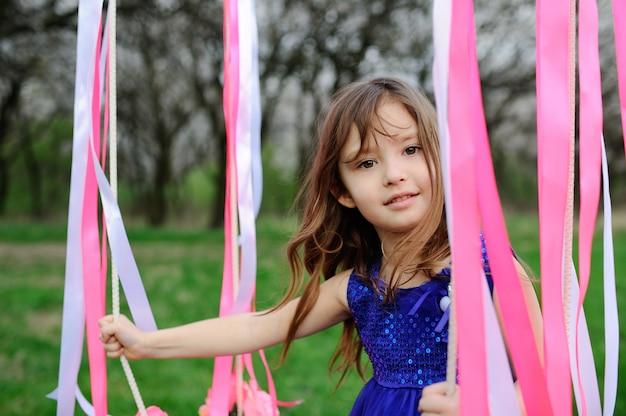 Belle petite fille monter sur une balançoire