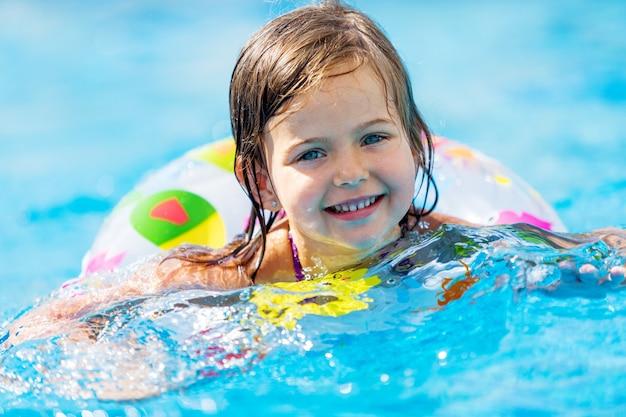 Belle petite fille nageant à la piscine