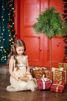 Belle petite fille ouvrant une boîte de cadeau de noël. célébration de noël et du nouvel an.