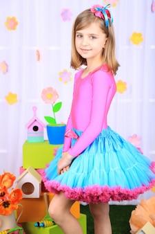Belle petite fille en petite jupe sur fond décoratif