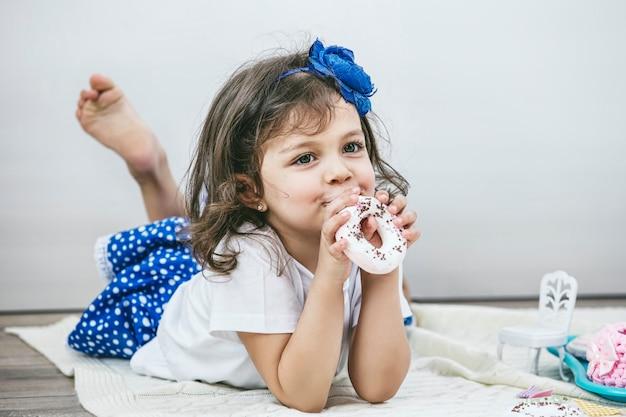 Belle petite fille avec des plats de jouets, des bonbons et des poupées joue au goûter heureux