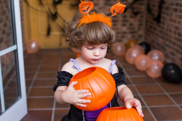 Belle petite fille portant un costume d'halloween. jouer avec des citrouilles