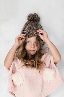 Belle petite fille posant avec un chapeau d'hiver