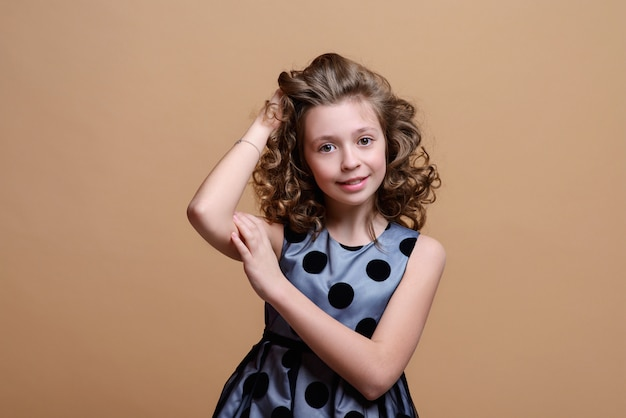 Belle petite fille posant largement et posant sur beige