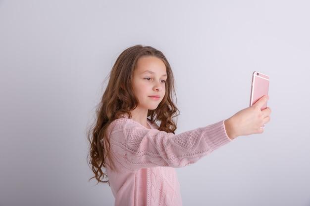 Belle petite fille prenant des photos d'elle-même avec téléphone portable, selfie