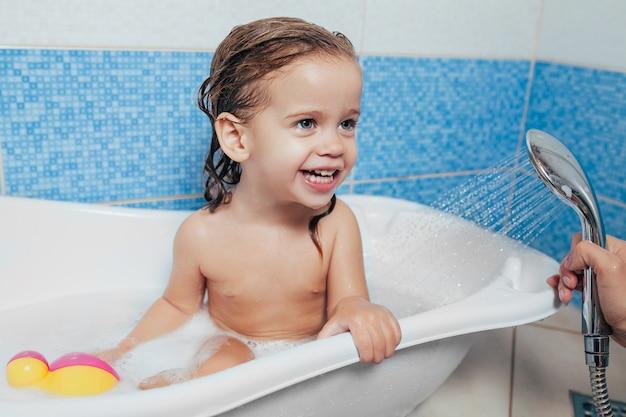 Belle petite fille prendre un bain à la maison.
