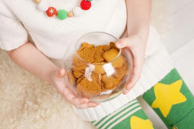 Belle petite fille en pull blanc tricoté tenant la plaque avec de savoureux biscuits en pain d'épice, vue en gros. période de noël. nouvel an et vacances d'hiver