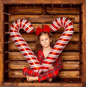 Une belle petite fille en pyjama de noël détient de gros bonbons au caramel sur un fond en bois dans sa main