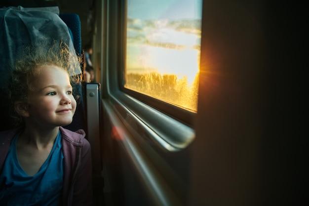 Belle petite fille regardant par la fenêtre du train à l'extérieur
