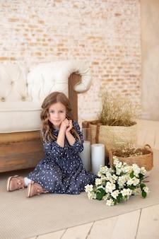Belle petite fille regardant avec un sourire adorable jolie petite fille aux cheveux bouclés