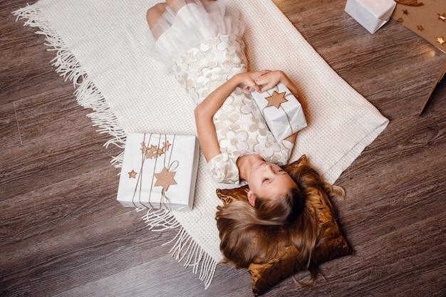 Belle petite fille rêve de cadeaux de noël. décorations de noël rouges, insolites. la veille de noël, le réveillon de noël