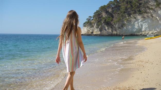 Belle petite fille en robe à la plage s'amuser. fille drôle profiter des vacances d'été.