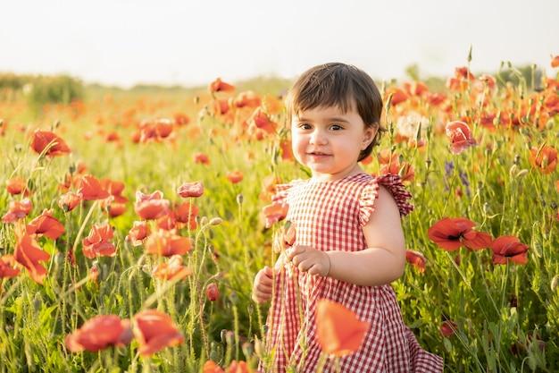 Belle petite fille en robe rouge sur champ de coquelicots au coucher du soleil d'été.