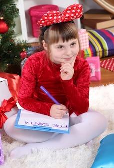 Belle petite fille en robe rouge écrit une lettre au père noël dans une pièce décorée de façon festive