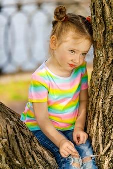 Belle petite fille rousse assise sur un arbre