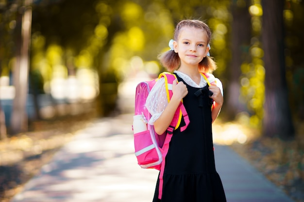 Belle petite fille avec sac à dos marchant dans le parc