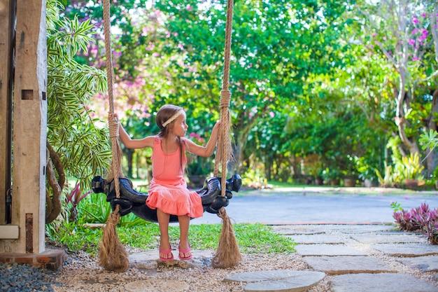 Belle petite fille se balançant sur une balançoire dans une cour fleurie