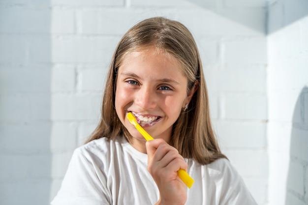 Belle petite fille se brosser les dents sur fond de mur de briques blanches