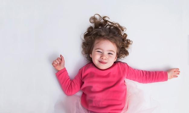 Belle petite fille se trouve sur le sol blanc et sourit. le concept d'une enfance heureuse.