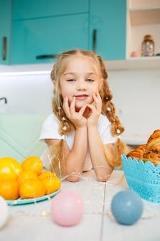 Belle petite fille de sept ans. assis à table dans la cuisine. vêtu d'un tee-shirt blanc. bonheur et joie sur le visage d'un enfant