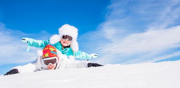 Belle petite fille avec son frère profitant de l'hiver