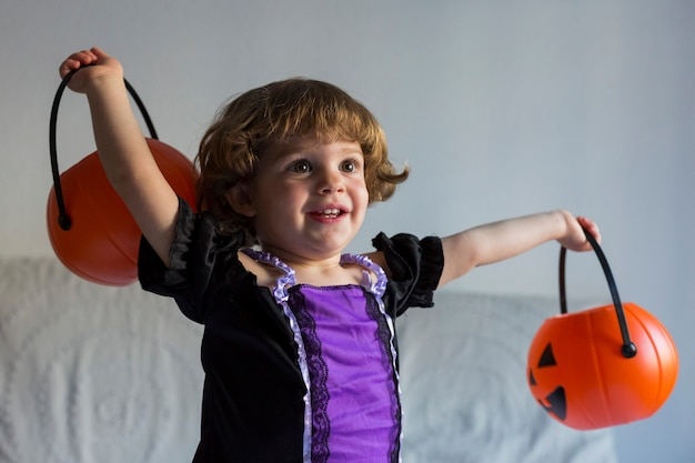 Belle petite fille souriante et portant le costume d'halloween. jouer avec des citrouilles