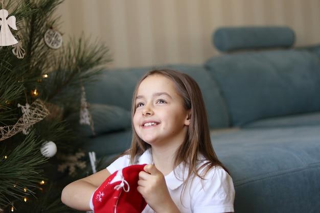 Belle petite fille souriante prenant des cadeaux de noël du sac traditionnel rouge avec espoir
