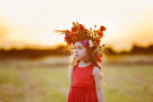 Belle petite fille souriante vêtue d'une robe rouge tourne avec une couronne sur la tête