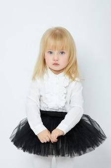 Belle petite fille sourit, enfant en vêtements d'automne pose sur fond blanc