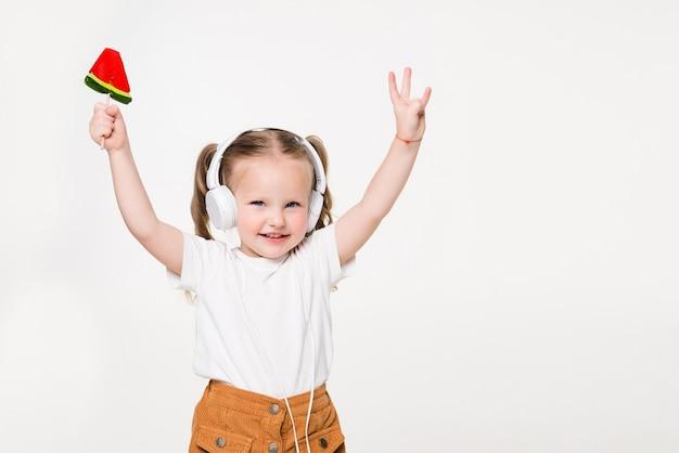 Belle petite fille avec sucette écouter de la musique dans un casque isolé