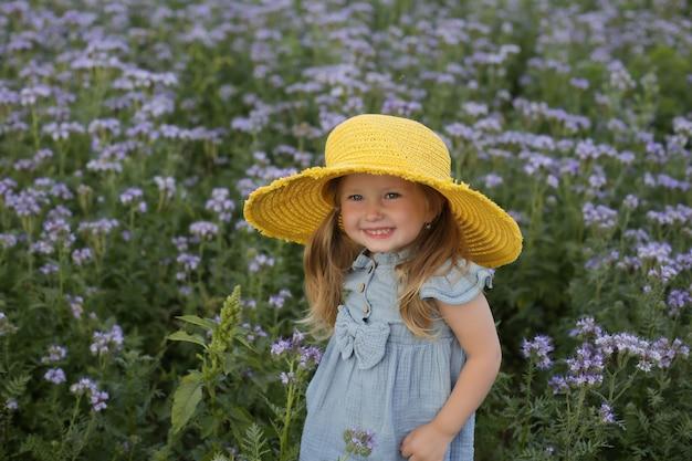 Une belle petite fille vêtue d'une robe bleue et d'un chapeau jaune se tient dans un champ de fleurs