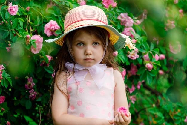 Une belle petite fille vêtue d'une robe rose et d'un chapeau dans le jardin avec des roses. photo de haute qualité