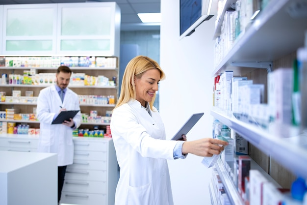Belle pharmacienne blonde vérifiant la disponibilité des médicaments pour l'achat en ligne et la vente de médicaments en ligne.