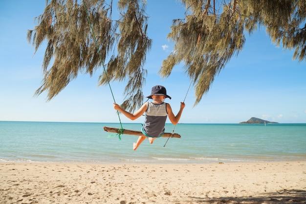 Belle photo d'un bébé assis sur un pendule sur la plage