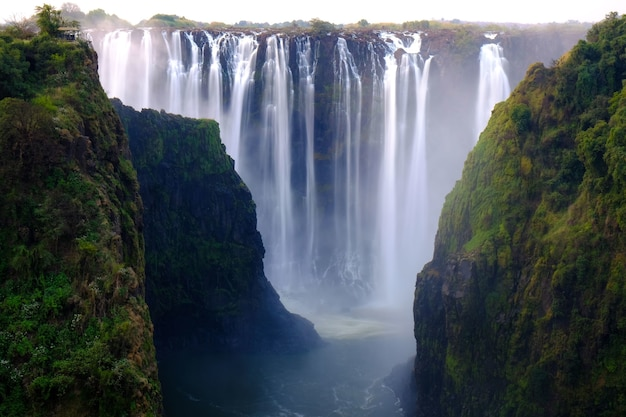 Belle photo d'une cascade entourée d'arbres et de collines