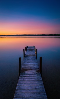 Belle photo de couleurs du coucher du soleil à l'horizon d'un lac tranquille avec un quai