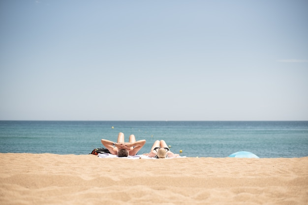 Belle photo d'un couple se relaxant et se faisant bronzer à la plage sous la lumière du soleil
