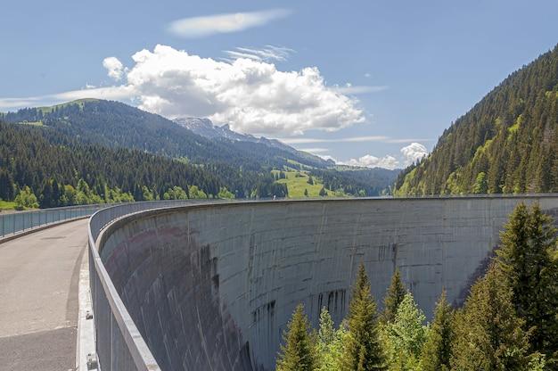 Belle photo du barrage du lac de l'hongrin avec des montagnes sous un ciel clair