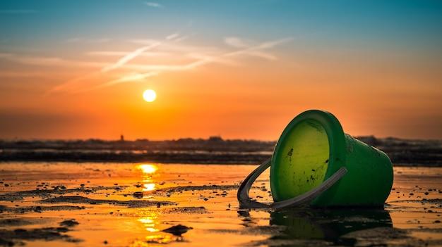Belle photo du coucher de soleil avec un seau vert au bord de la mer