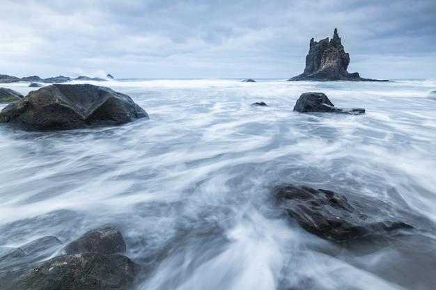 Belle photo d'eau qui coule autour de grosses pierres près du rocher de benijo par temps nuageux en espagne