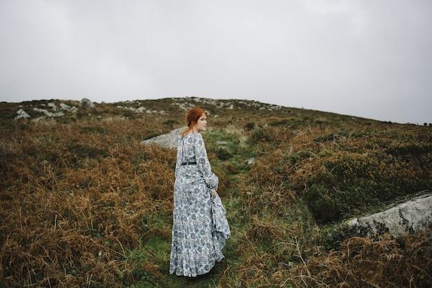 Belle photo d'une femme au gingembre avec une peau d'un blanc pur dans une jolie robe bleu clair