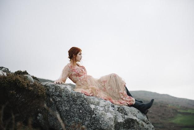 Belle photo d'une femme au gingembre avec une peau d'un blanc pur dans une jolie robe rose clair