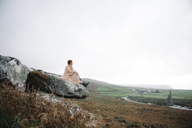 Belle photo d'une femme au gingembre avec une peau d'un blanc pur dans une jolie robe rose